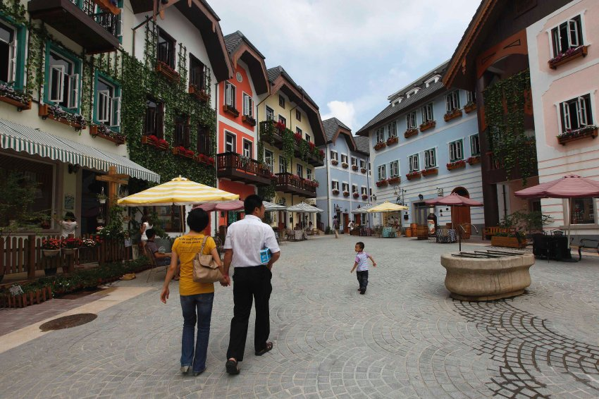 A family walks in the Chinese replica of Austria's UNESCO heritage site, Hallstatt village, in China's southern city of Huizhou